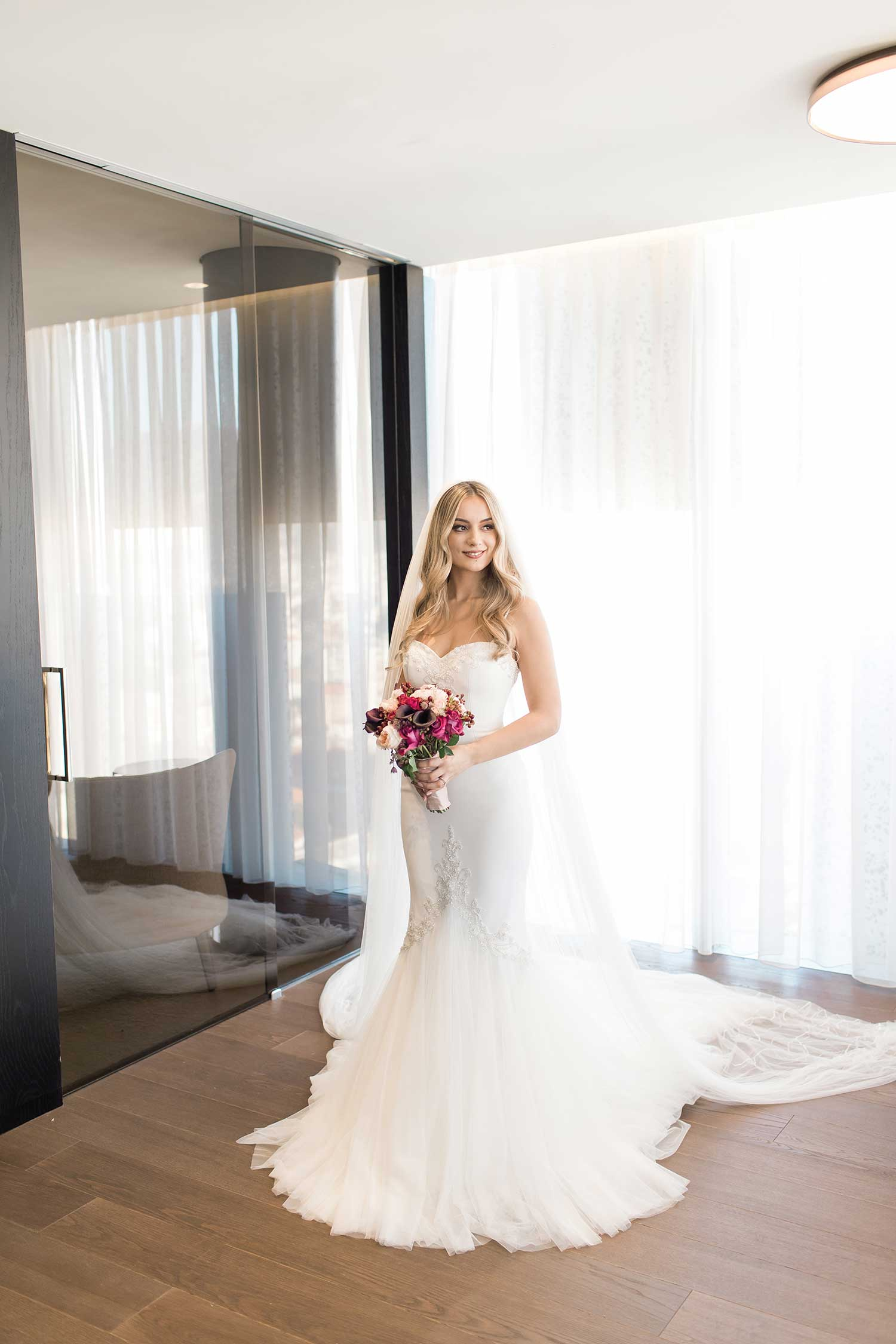 Bride with her white wedding dress,veil and flower bouquet