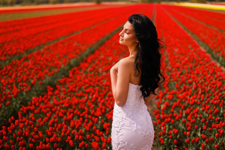 Lovely bride posing in red tulip field
