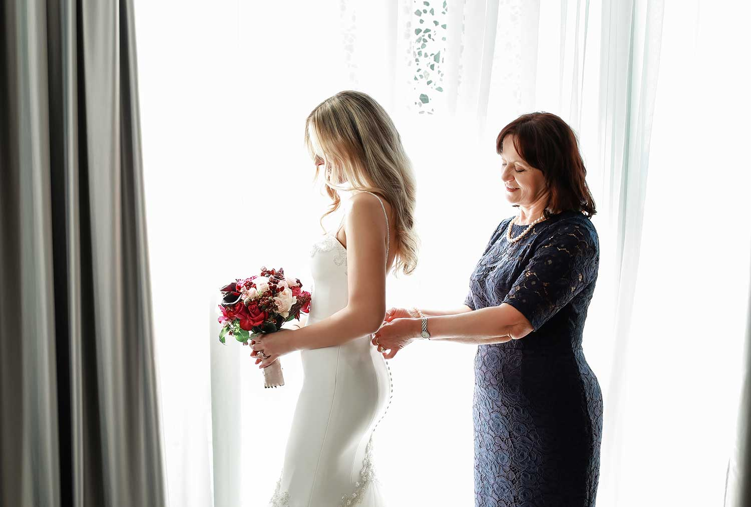 Mother helping the bride getting ready