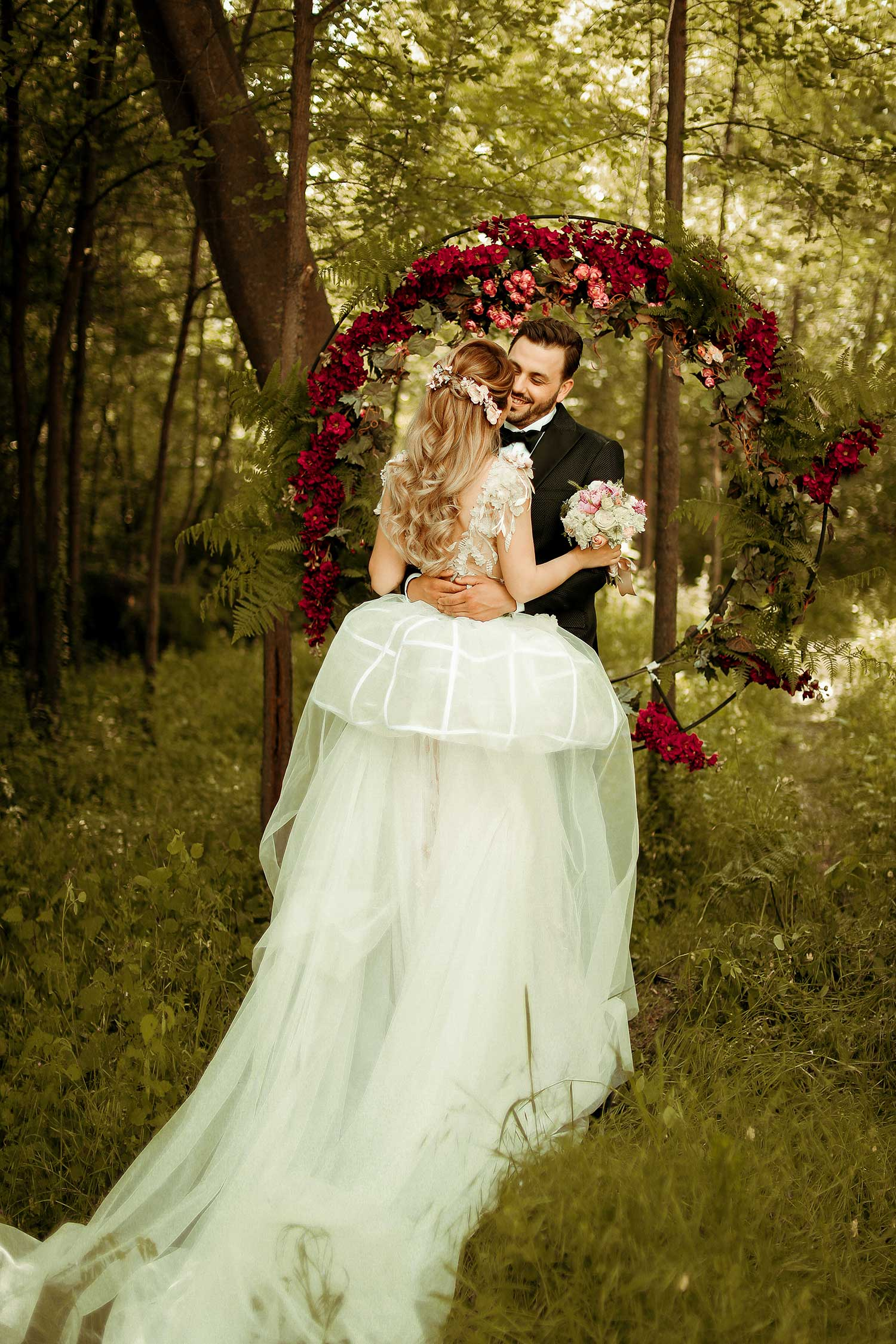 Bride and groom posing with red flowers