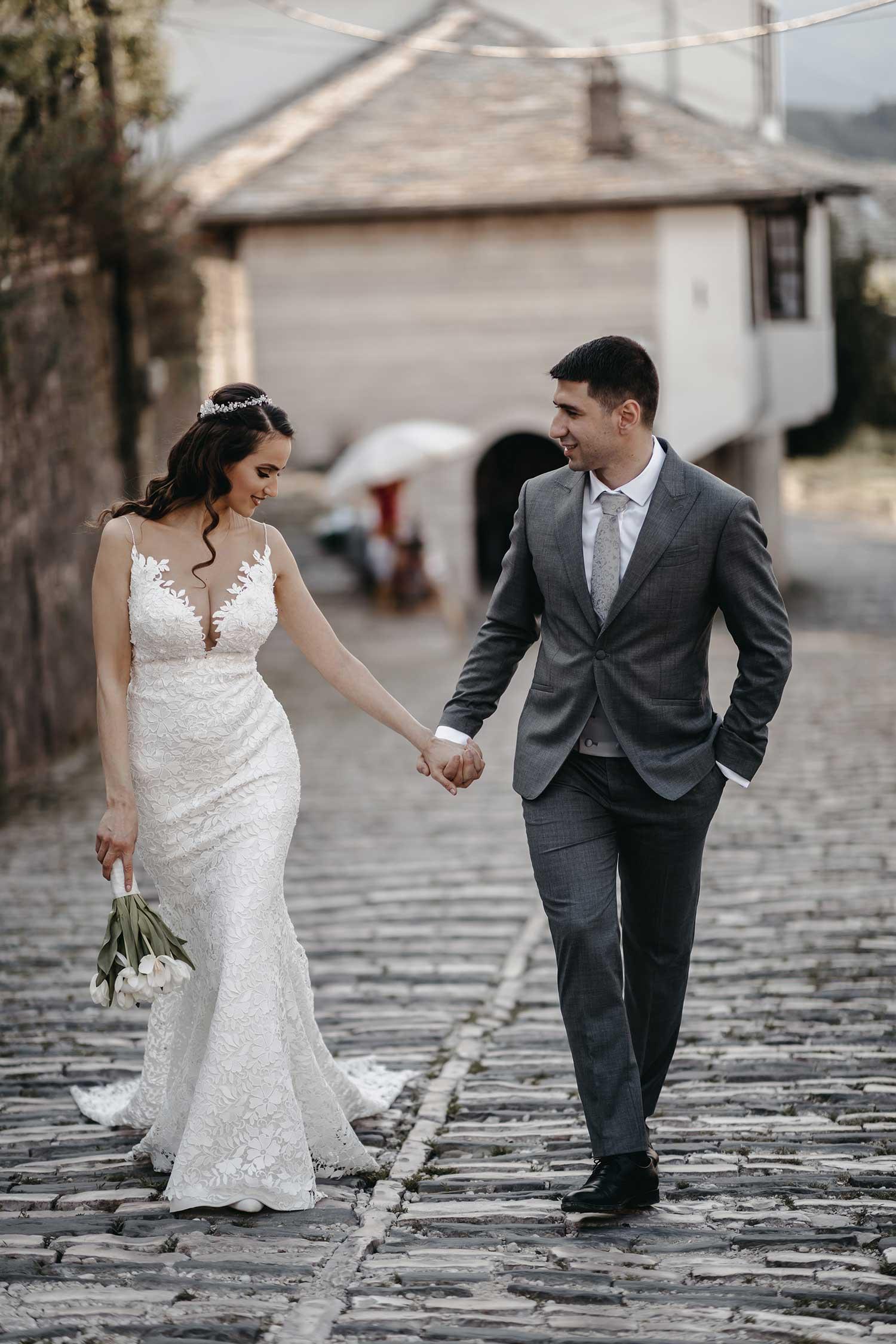Bride and groom walking down the streets of Gjirokaster