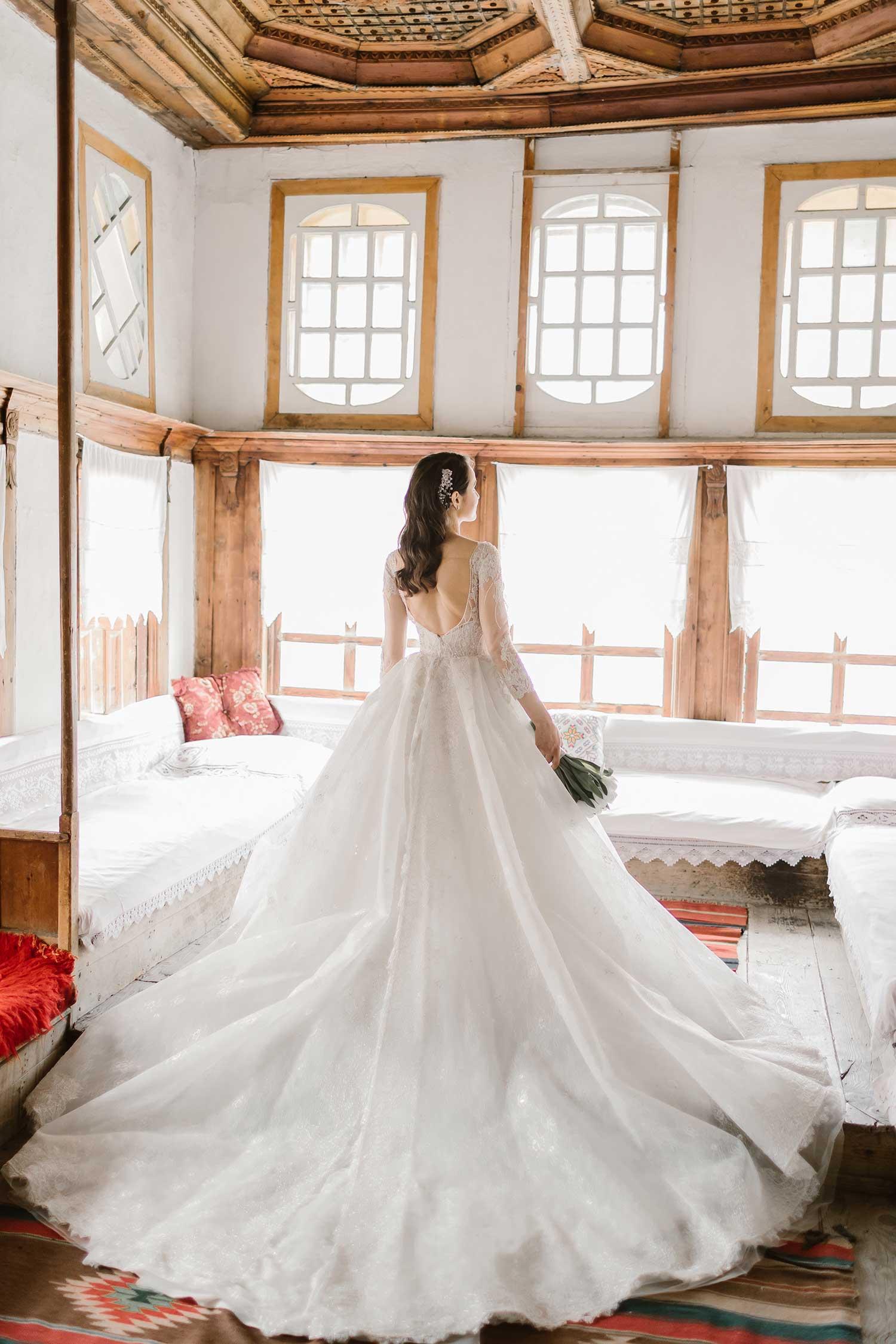 Bride posing with a wedding dress inside a house in Gjirokaster