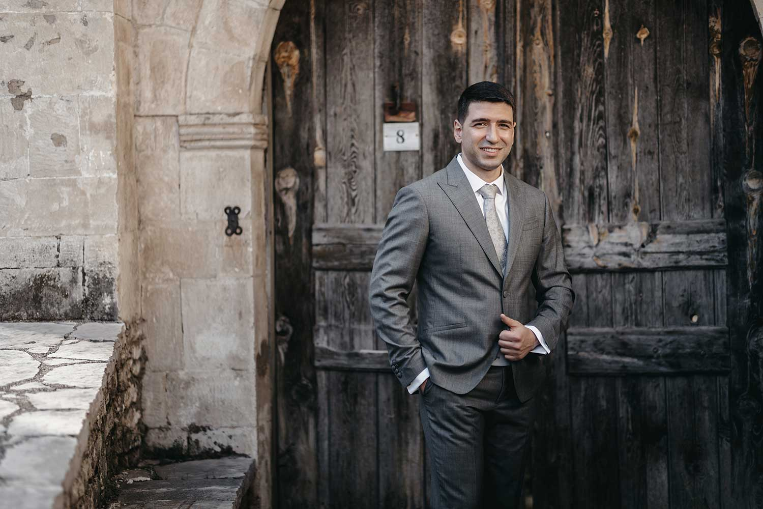 Groom posing in front of an old door