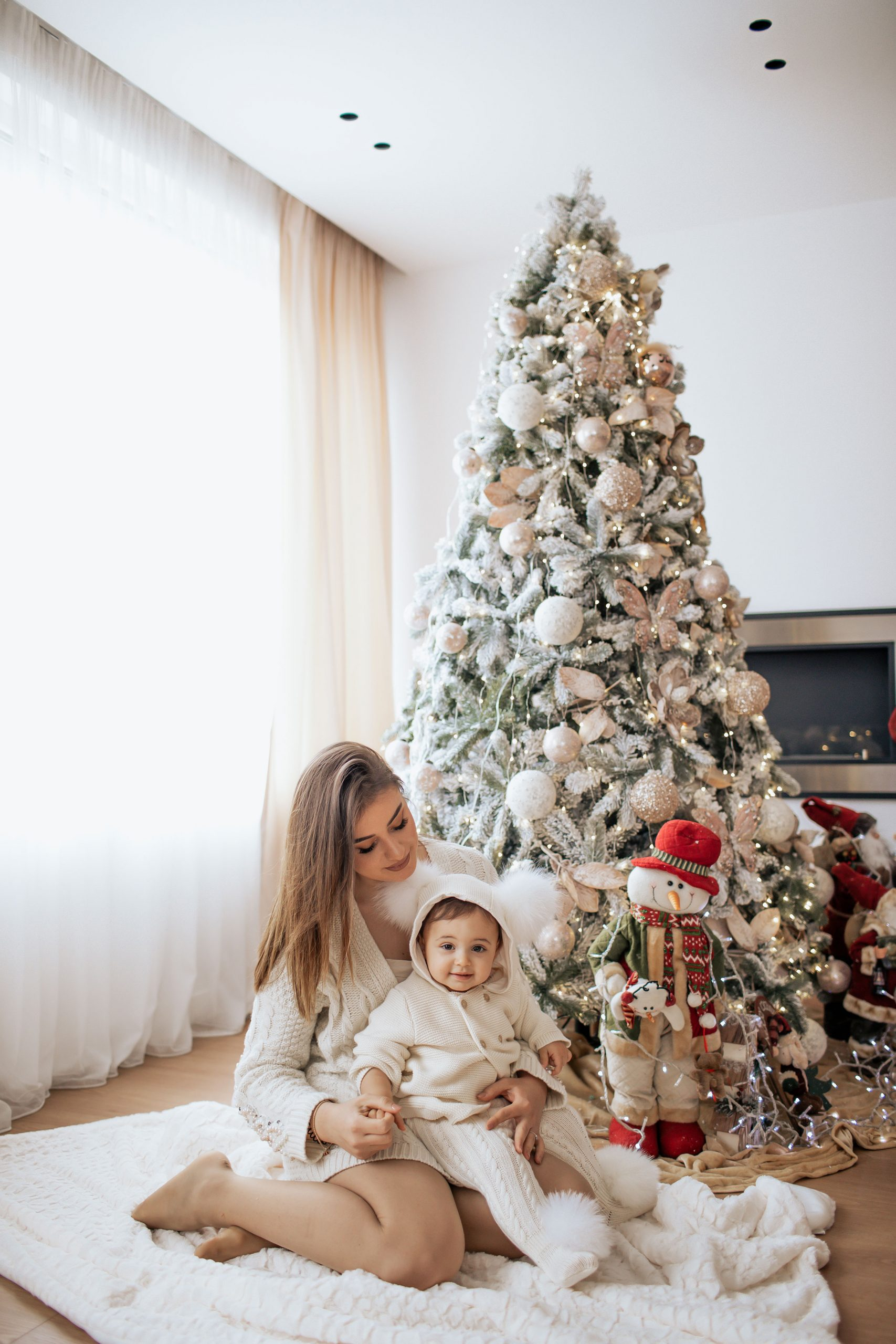 Mom and daughter posing near the Christmas tree wearing white outfits