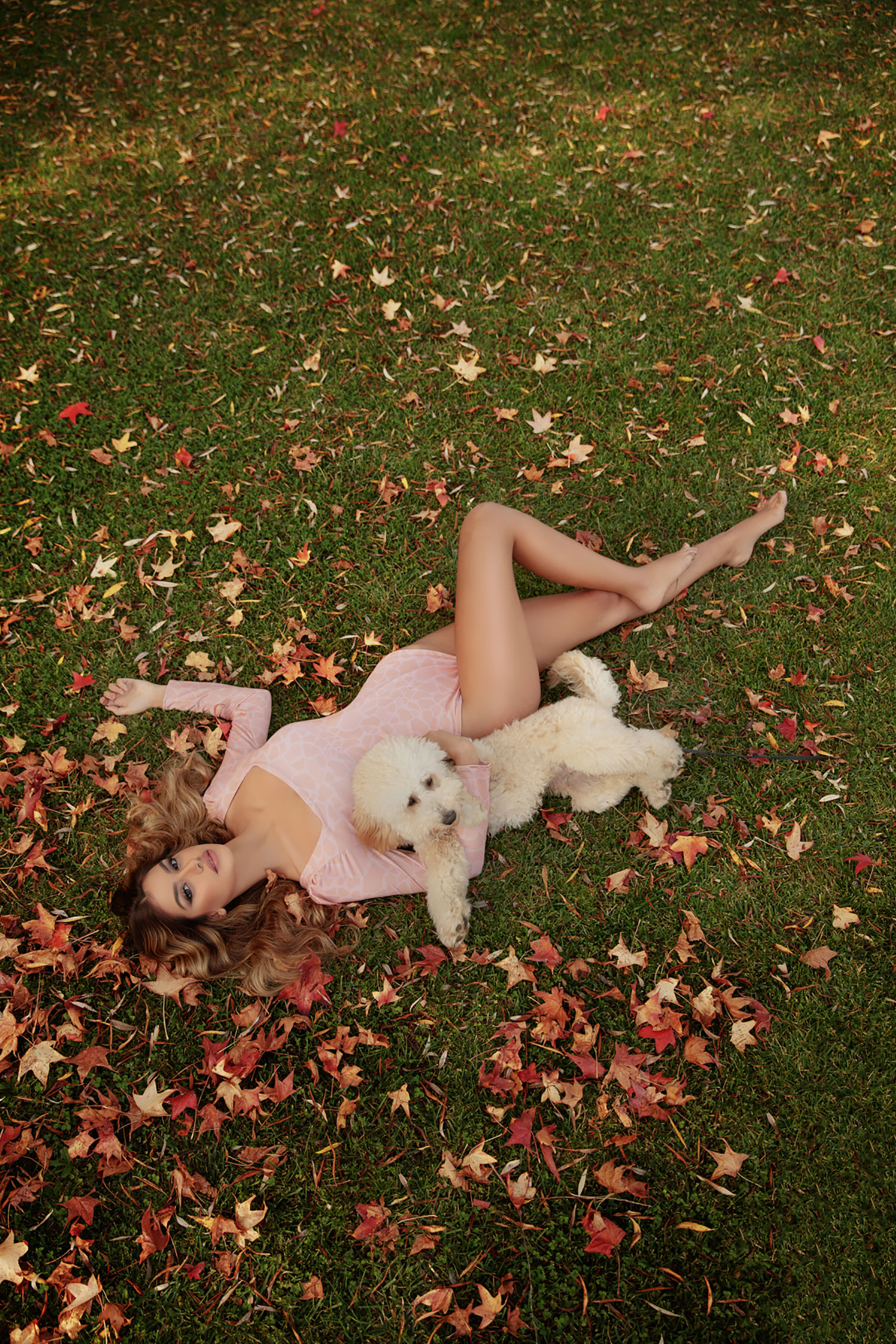 Model laying on the ground with a dog calendar photos