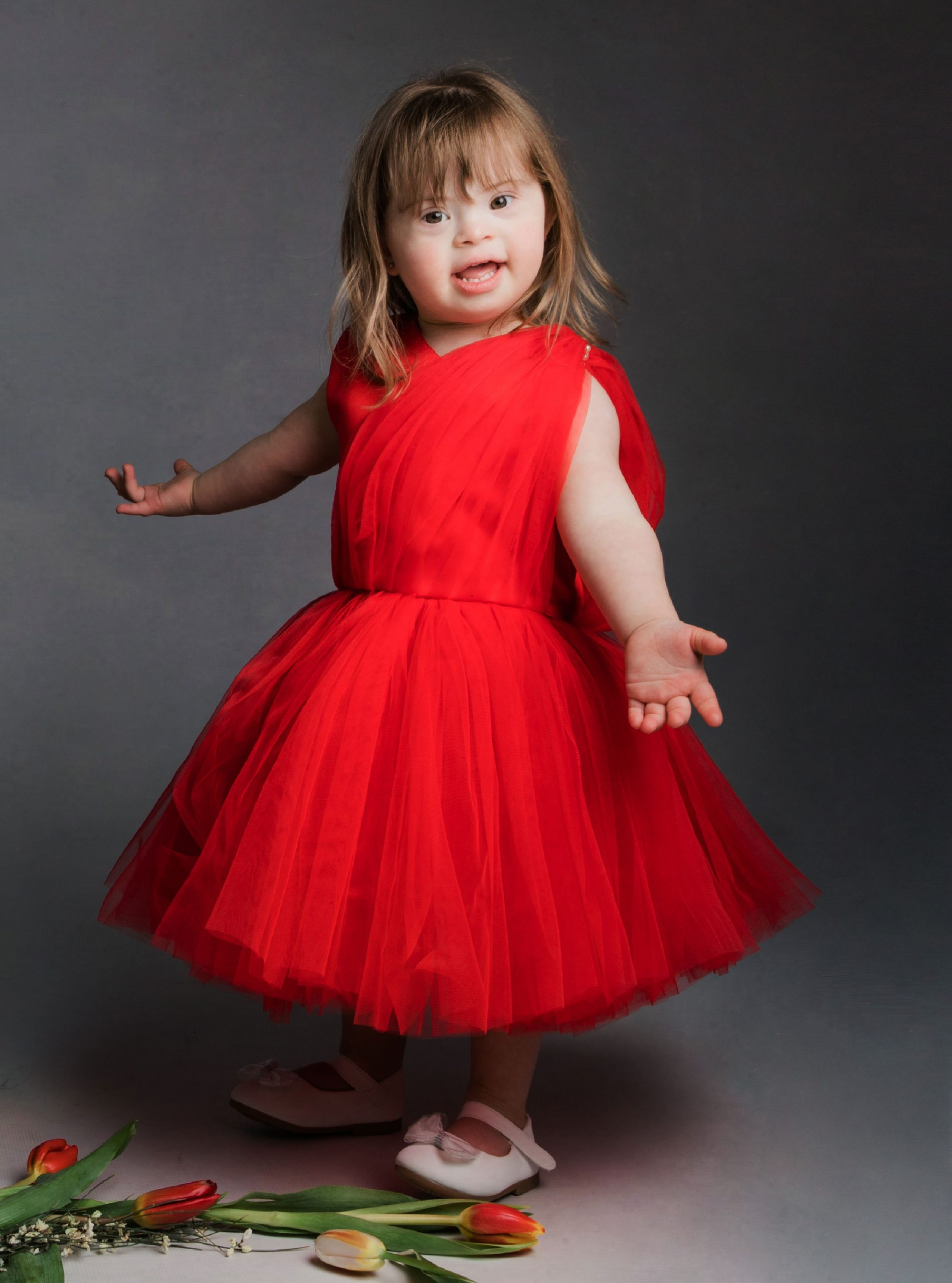 Little girl wearing a red tulle dress