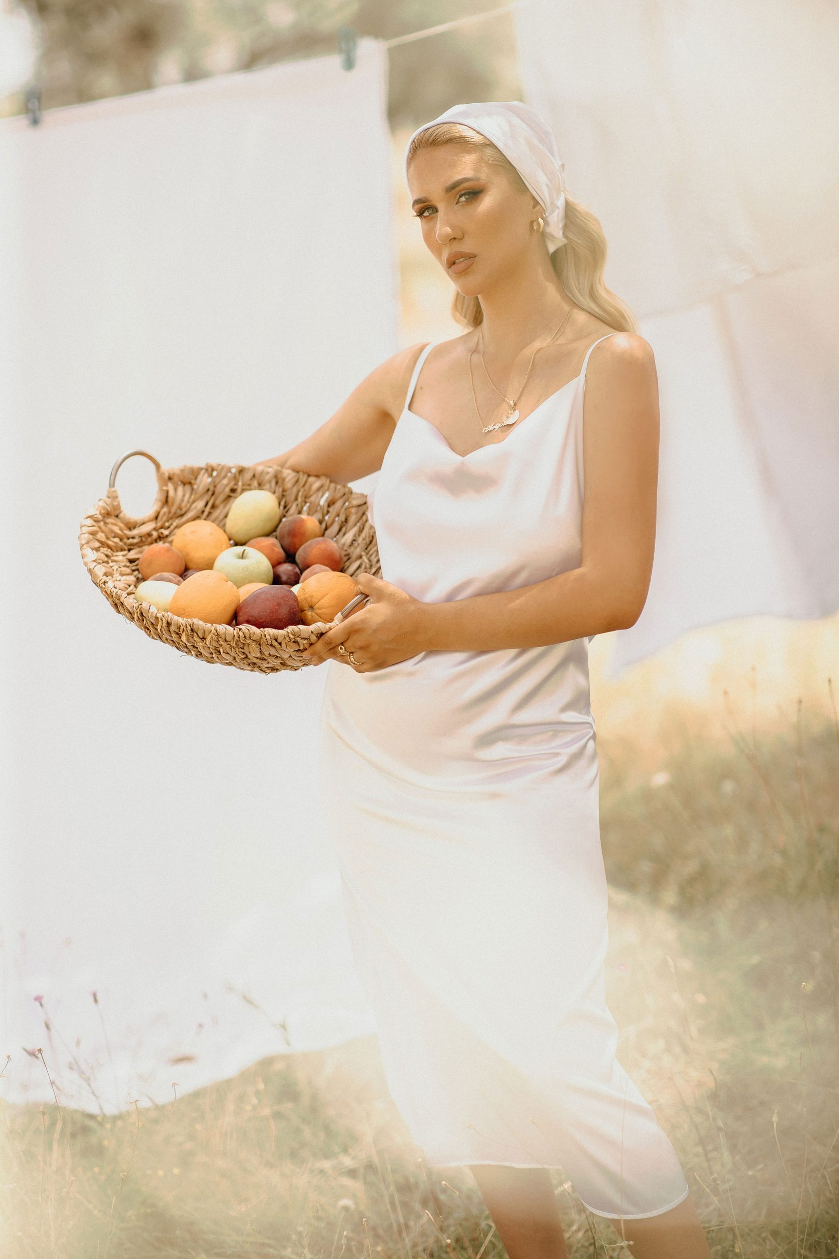 Beautiful girl holding fresh fruits in a field