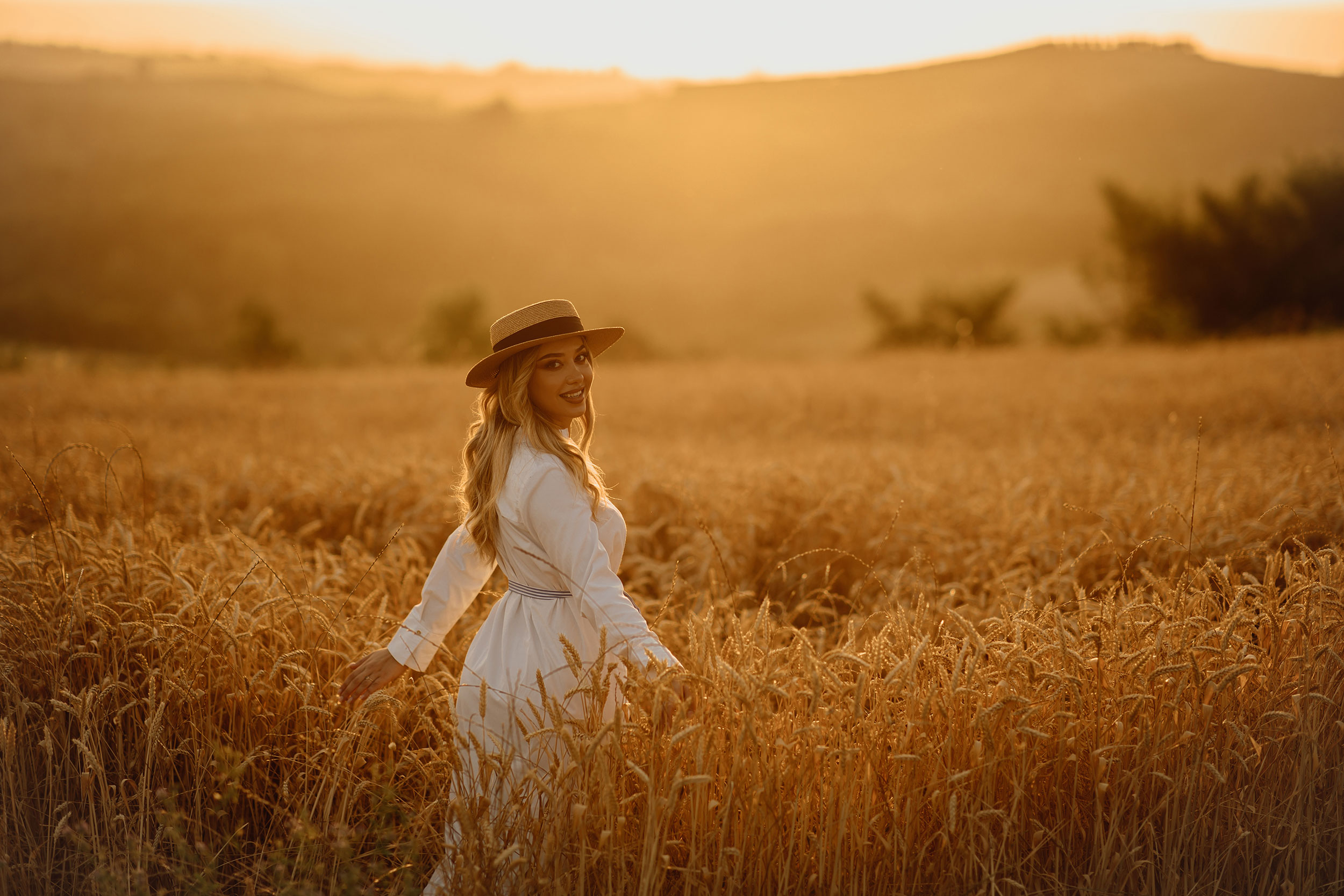 Adisa Gjo wearing a white dress and a hat during the photoshoot