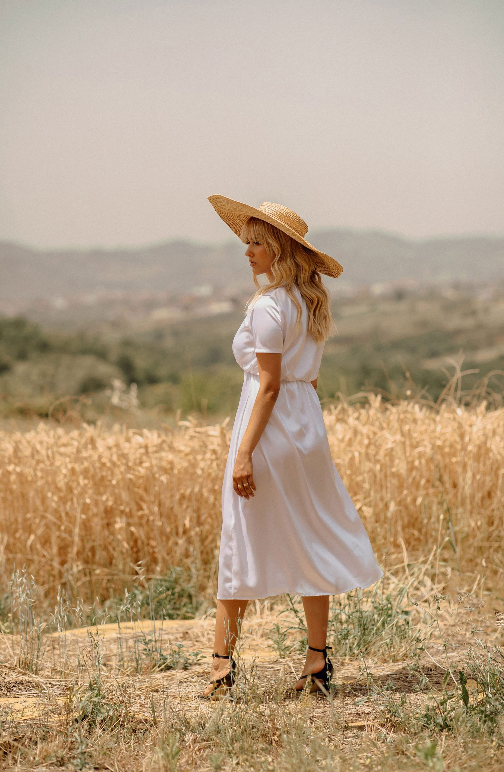 Blonde girl wearing a white dress and a hat in a Wheatfield