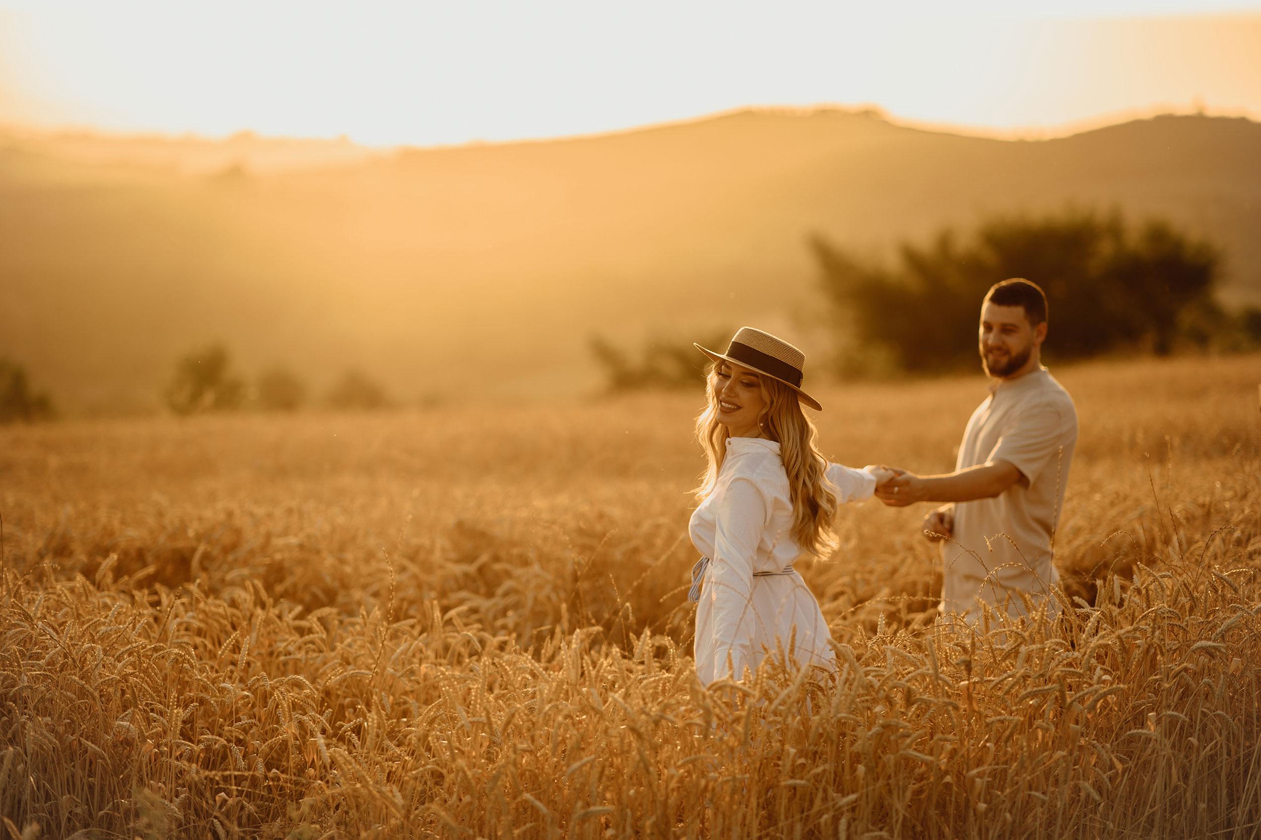 Boyfriend holding his girlfriend's hand in a golden field