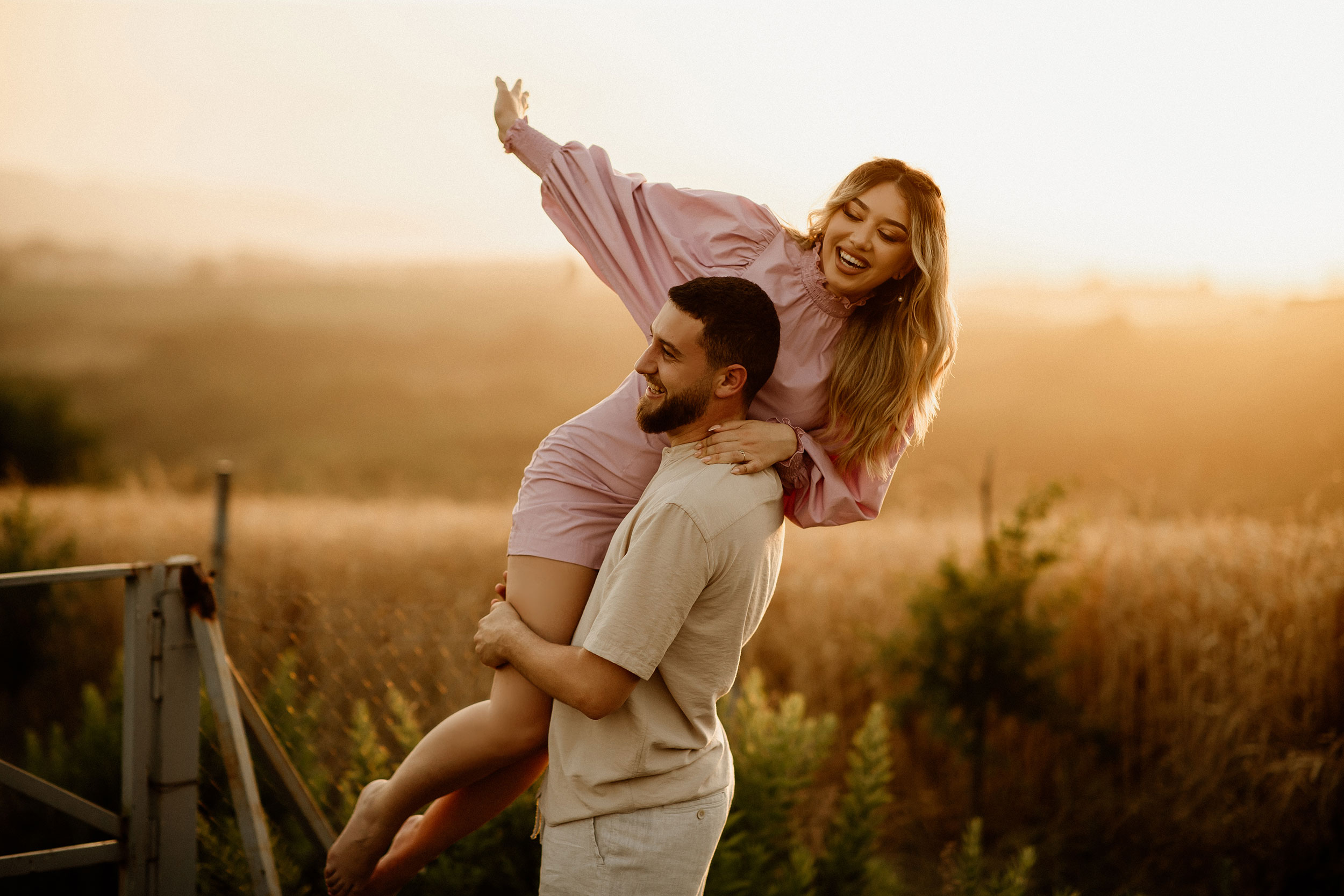 Boyfriend is lifting girlfriend in the air and holding her close