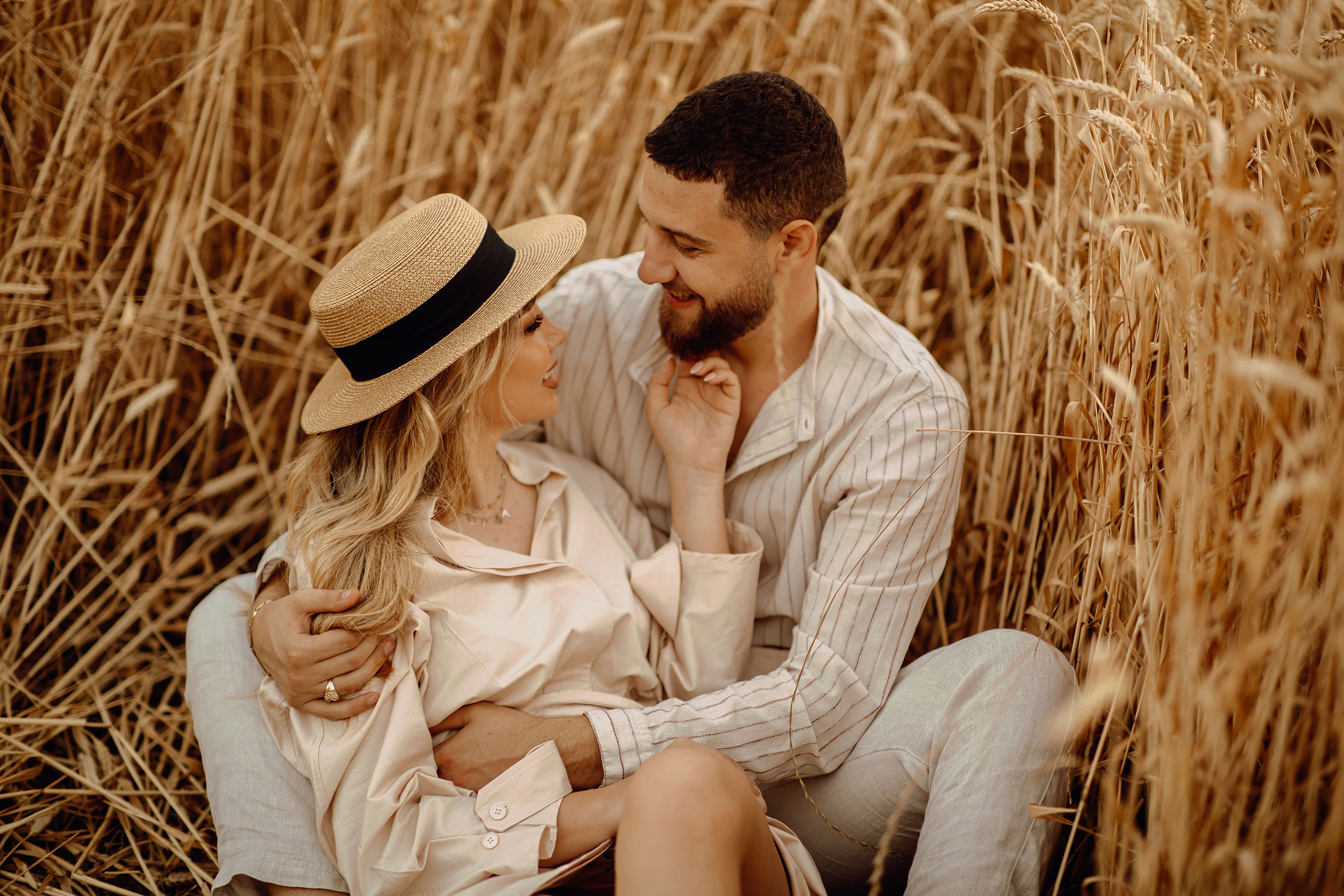 Couple looking into each other's eyes while sitting on a field