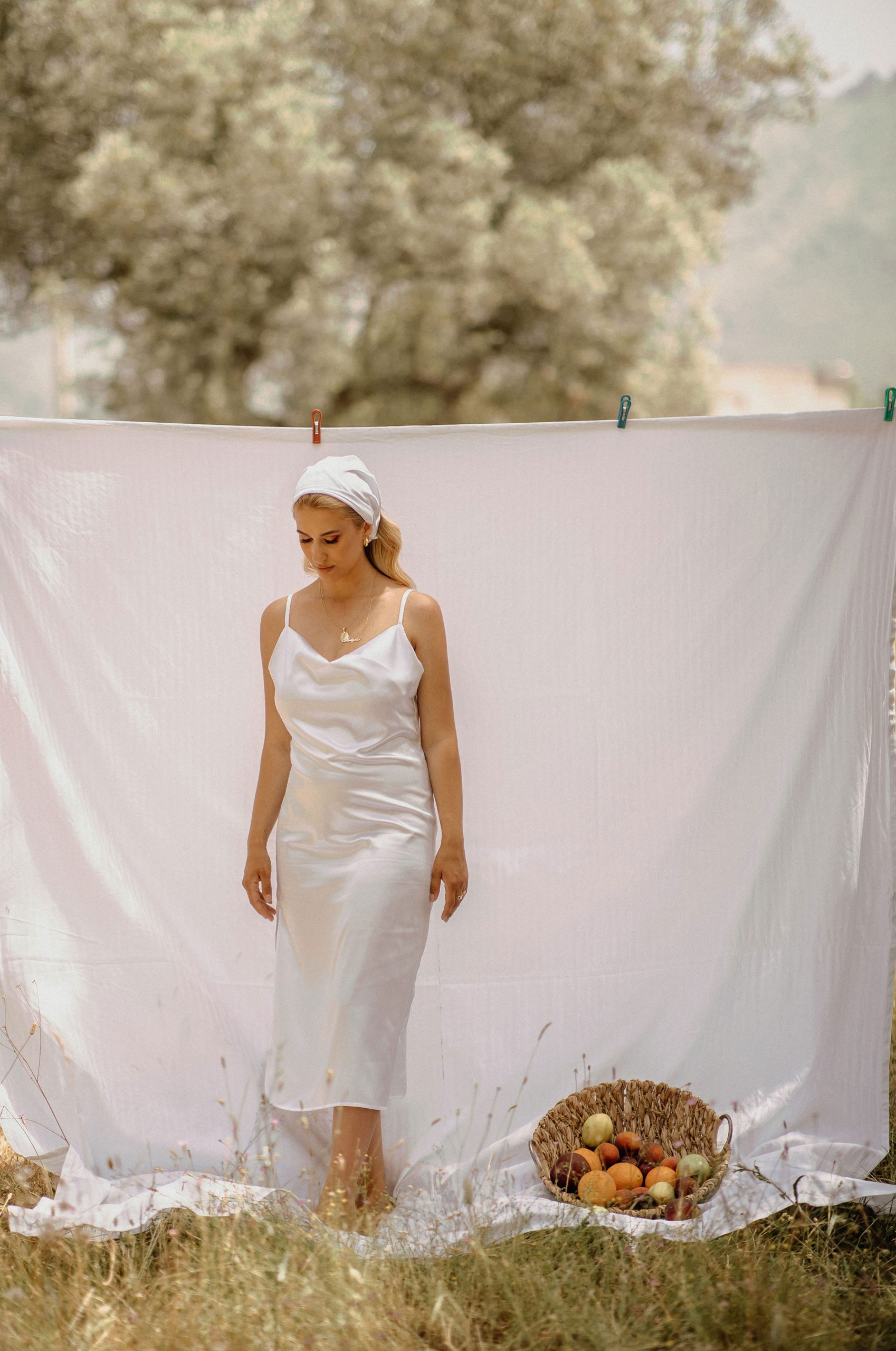 Girl staying near a white clothesline wearing white dress
