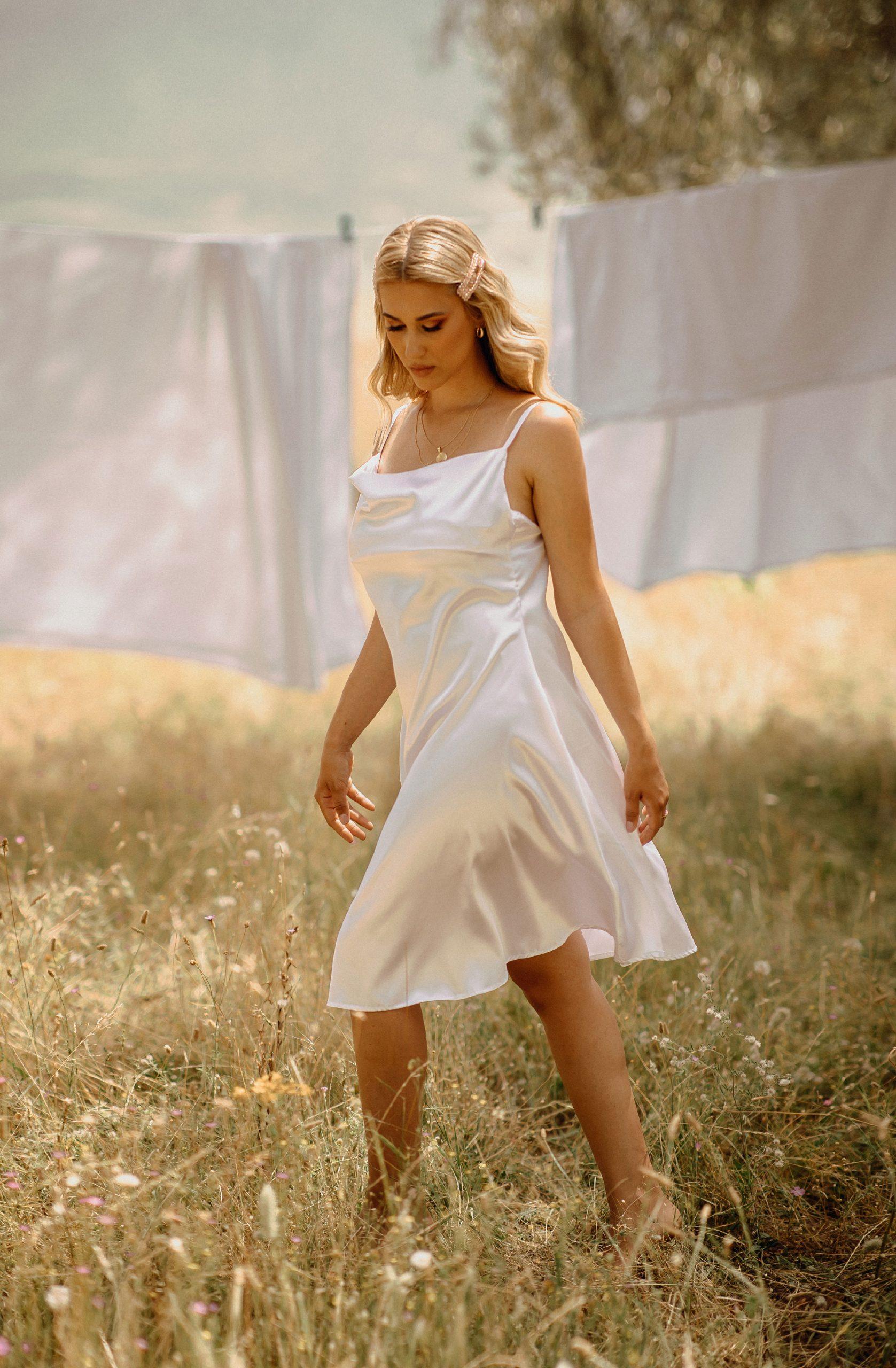 Girl walking in the field wearing a white dress