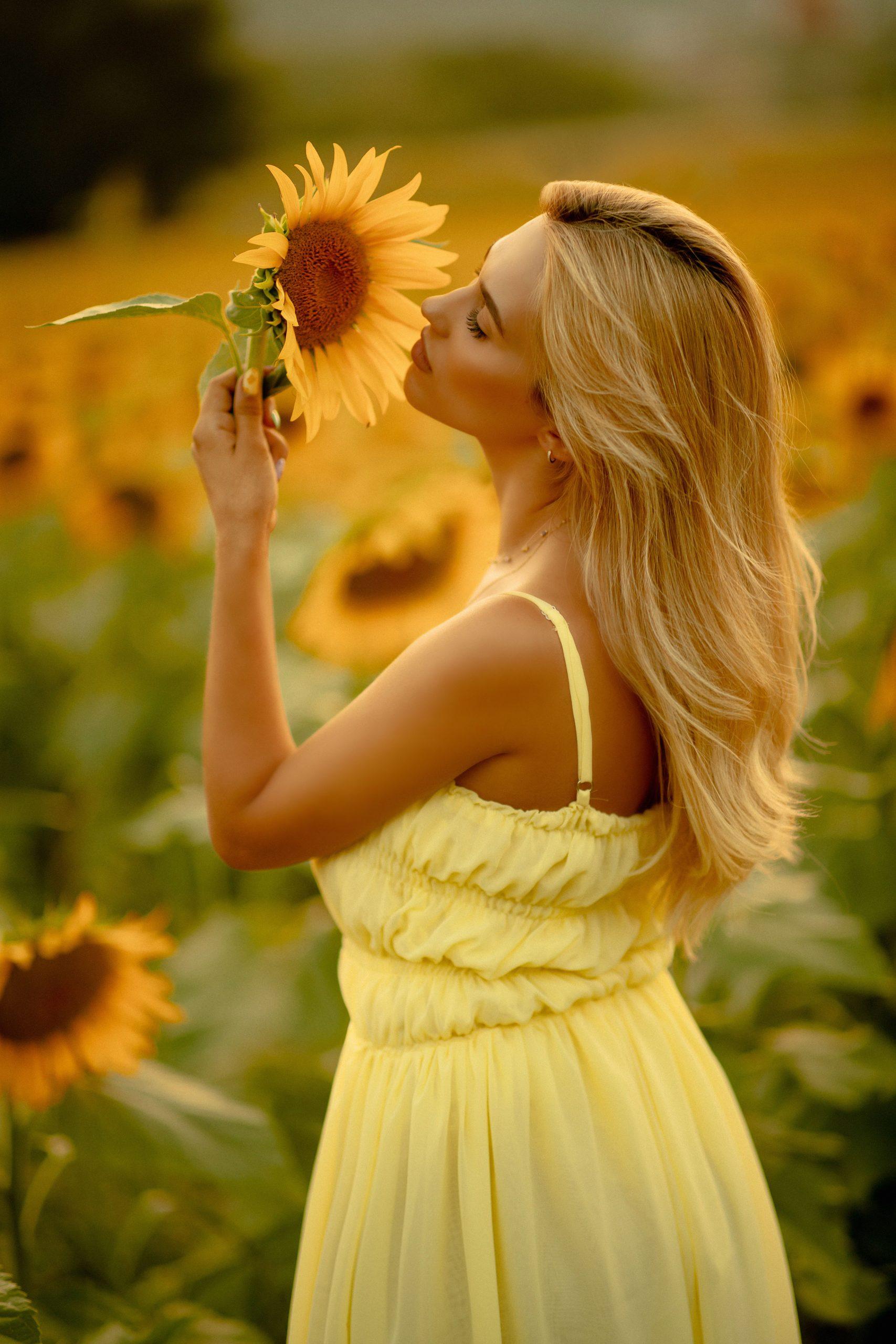 Blonde girl smelling the sunflower