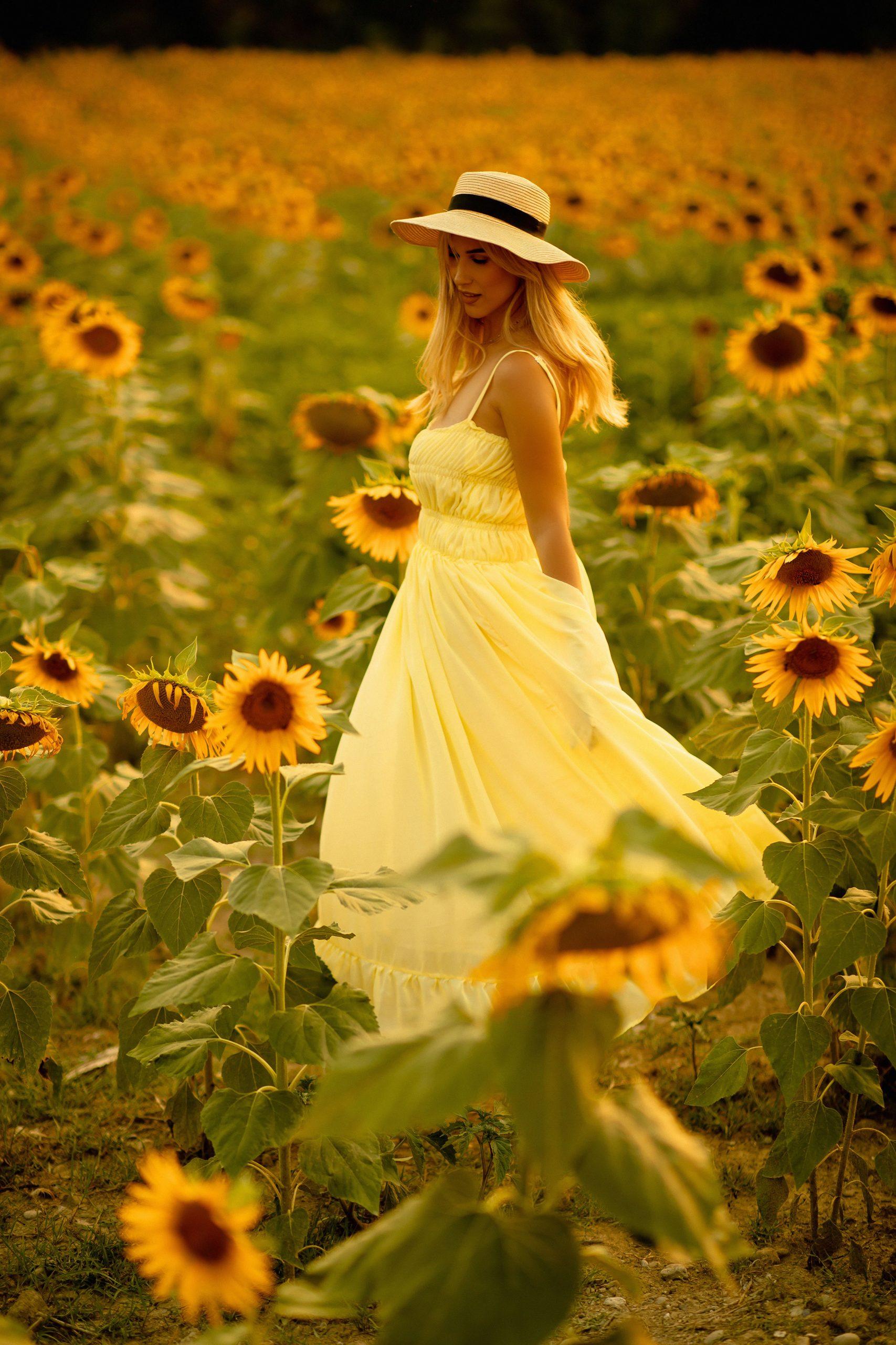Blonde girl spinning around in the sunflower field