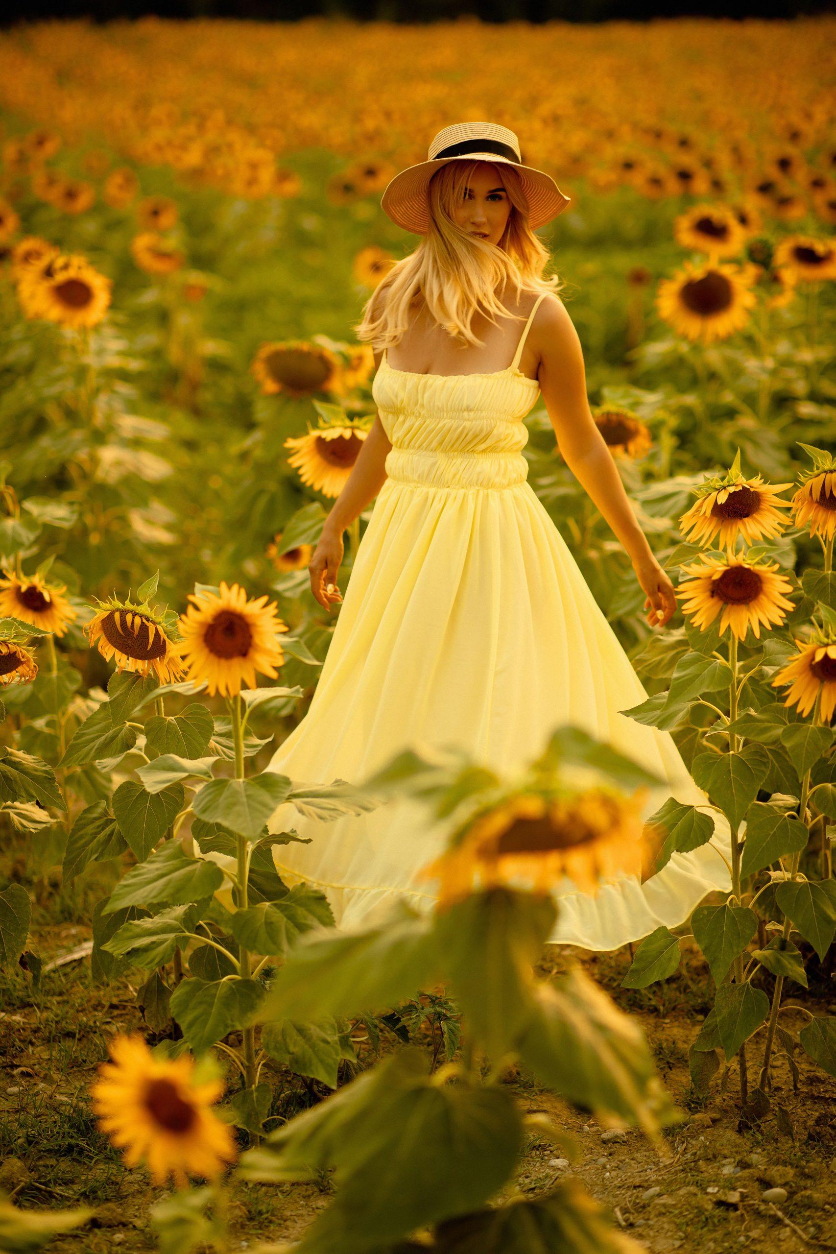 Blonde girl twirling in the sunflower field