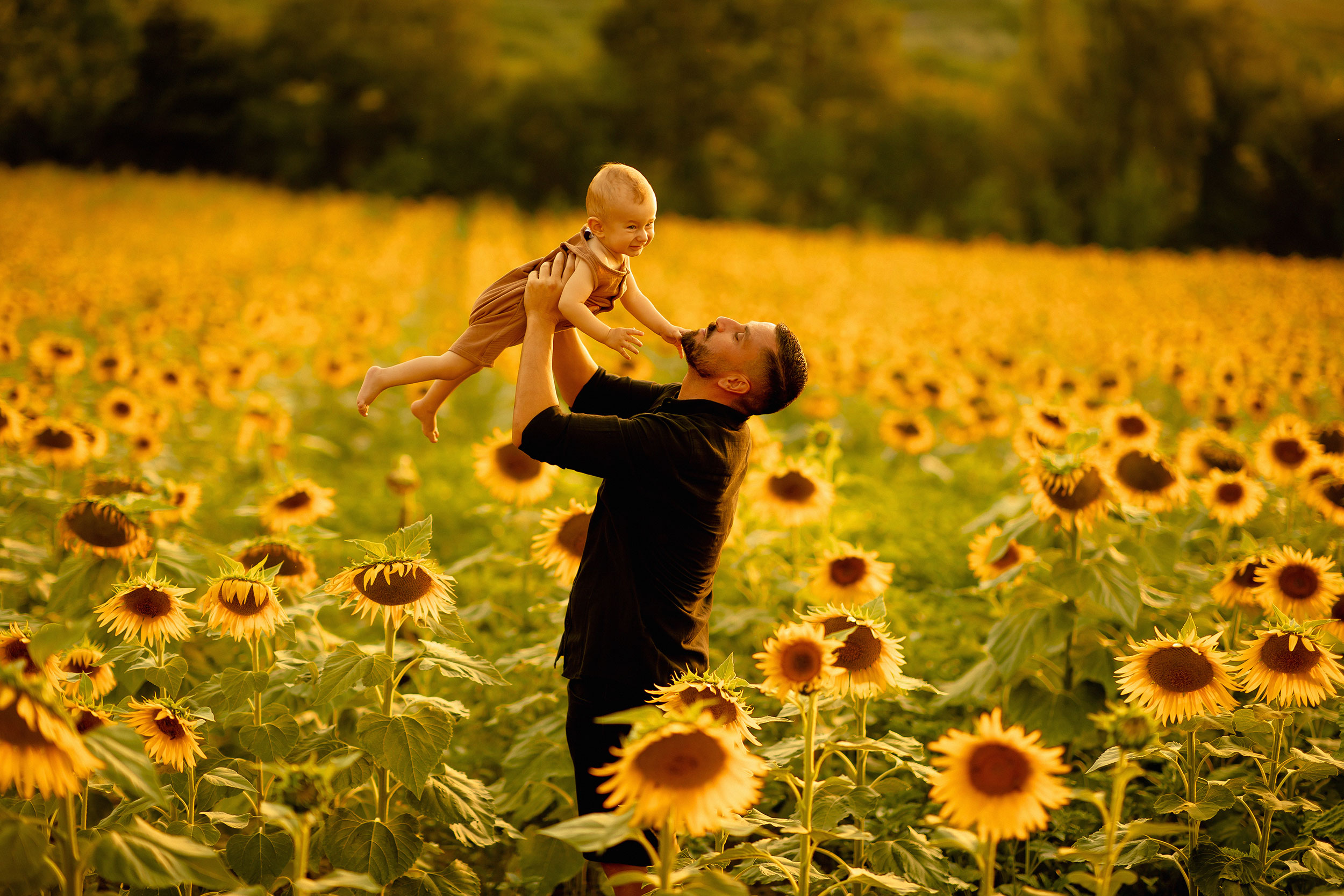 Father holding up his baby in nature