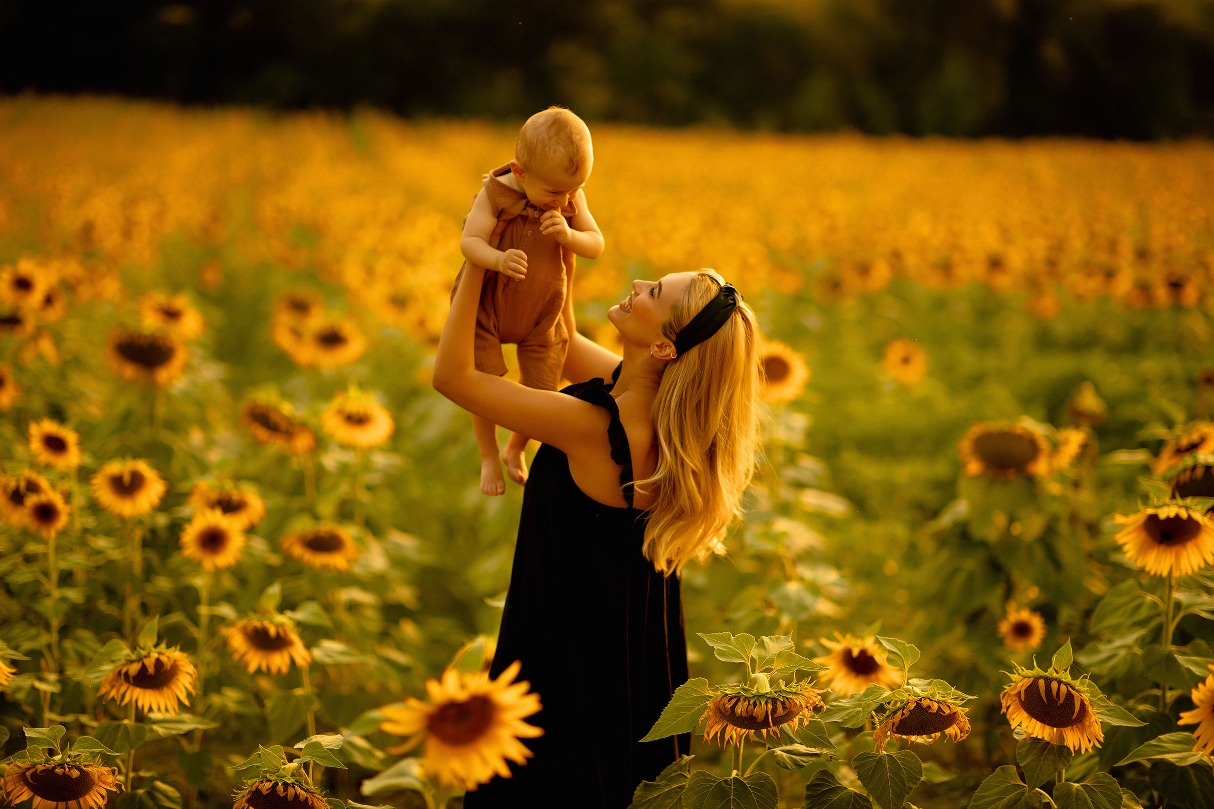 Mother holding her baby up in nature