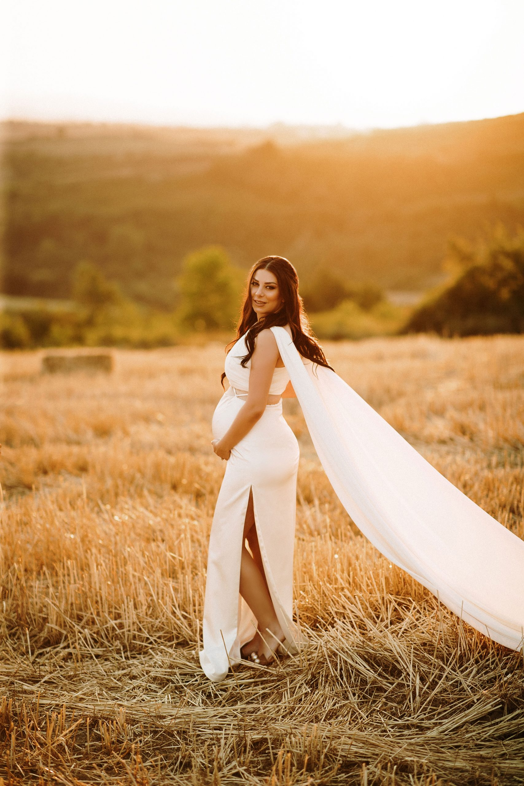 Mother to be posing with a white dress