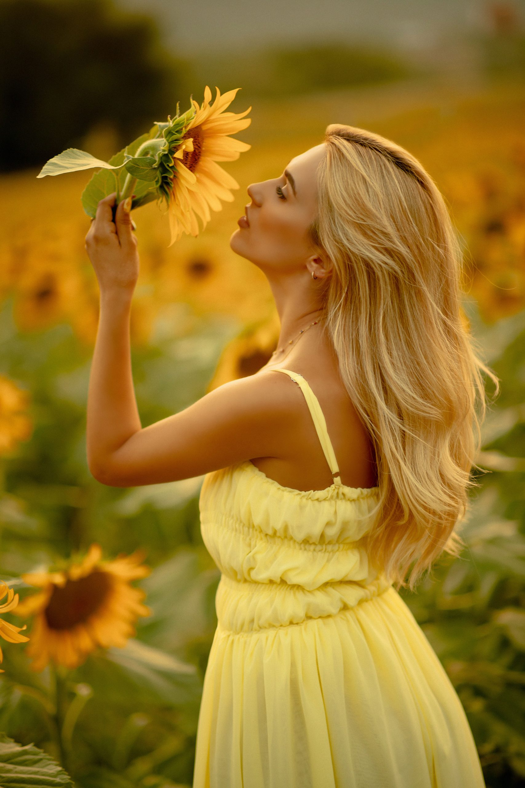 Posing during golden hour with a sunflower in her hand
