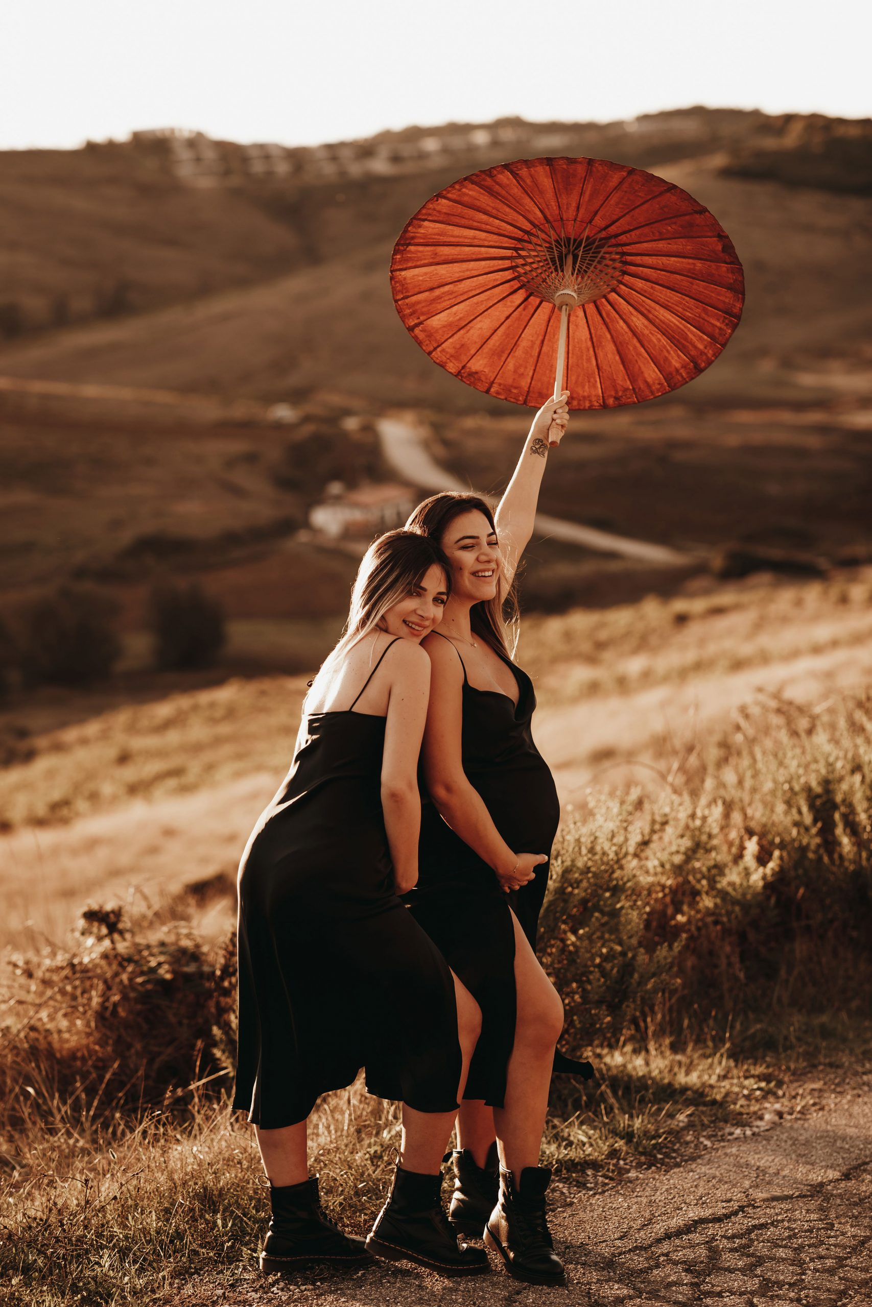 Sara Hoxha and her friend posing with an umbrella in nature during a maternity photo session