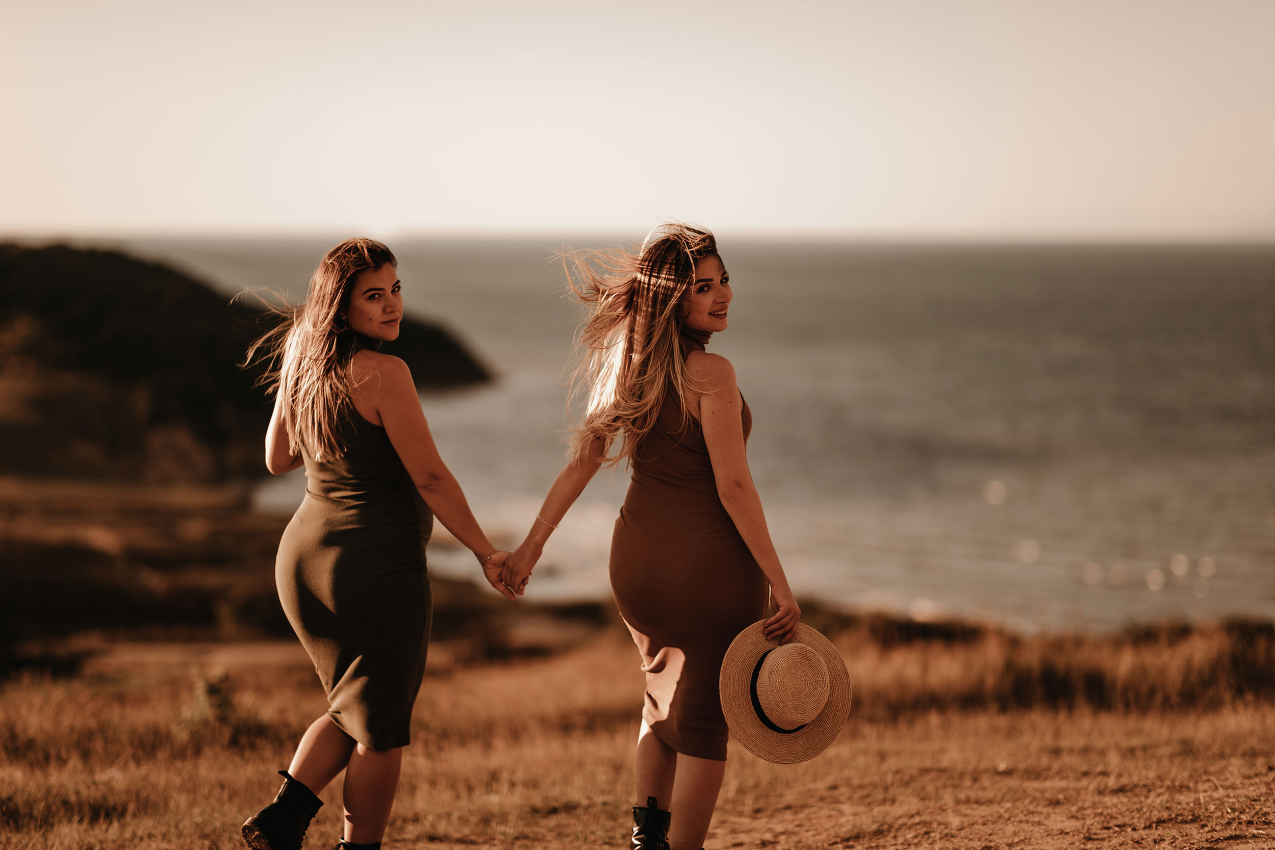 Two pregnant girls holding hand with each other looking at the camera