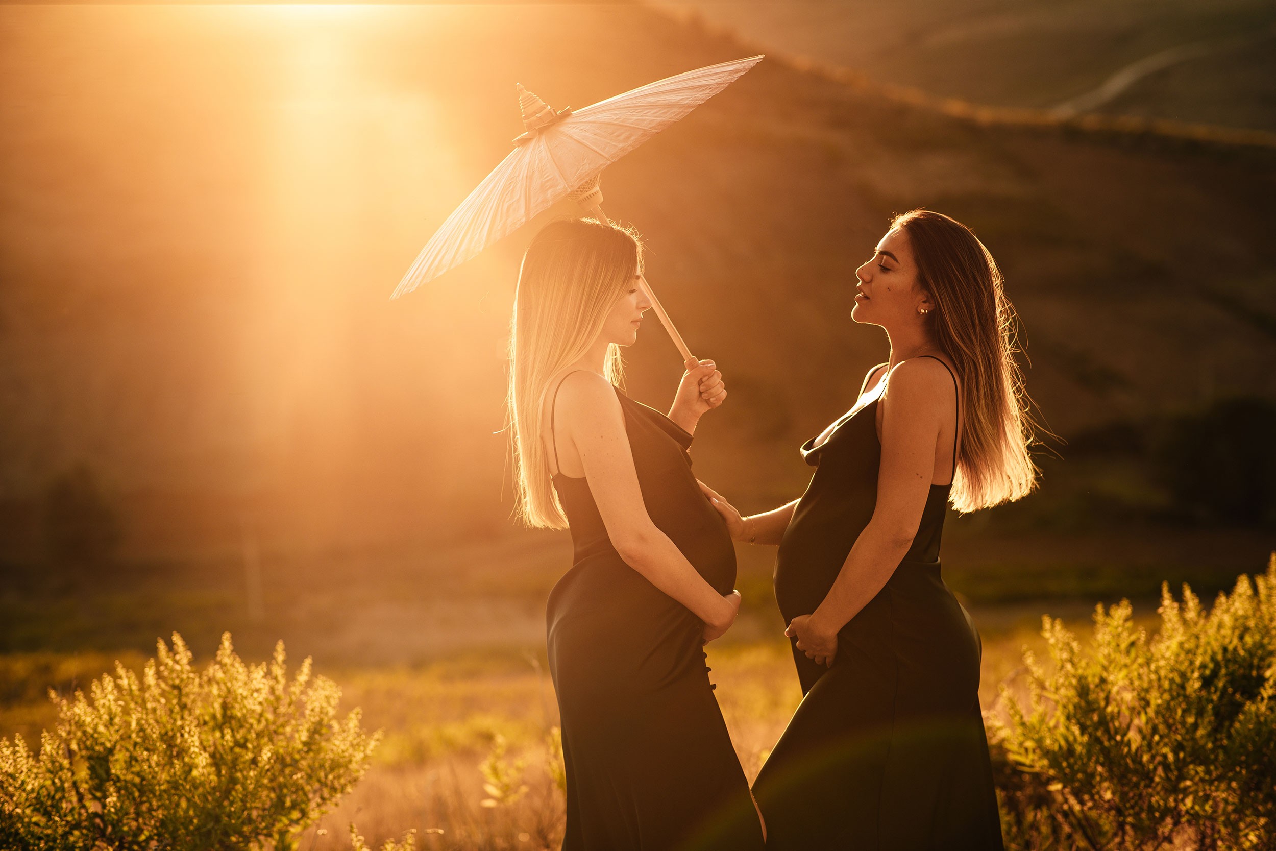 Two pregnant girls posing with an umbrella in nature