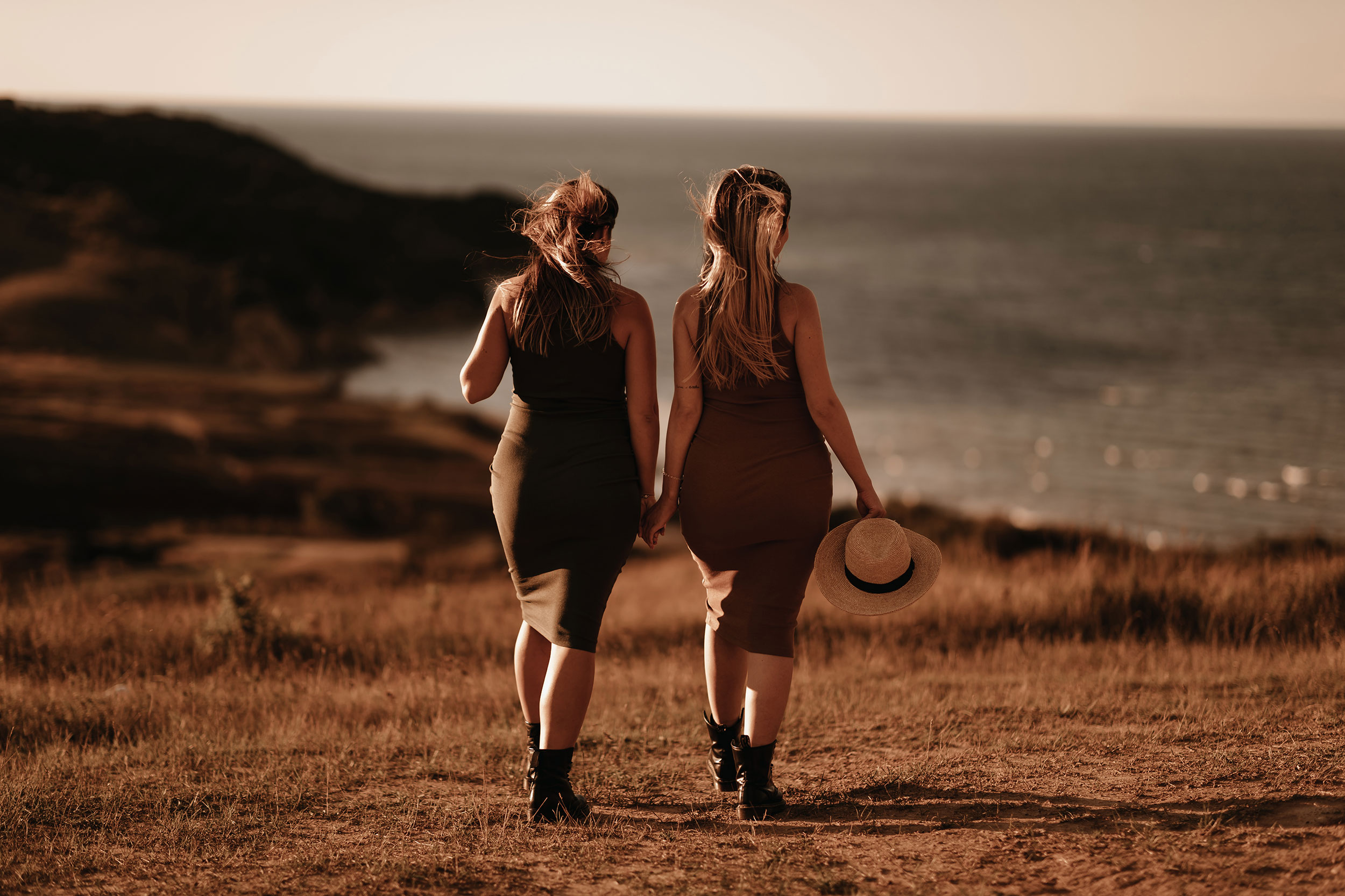 Two pregnant girls walking together towards the sea